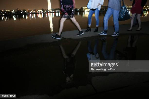 People walk by the Tidal Basin in Washington on March 25 2017 during the Cherry Blossoms season