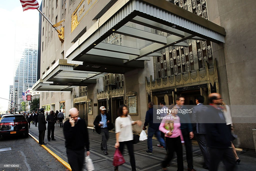 People walk by the Waldorf Astoria the landmark New York hotel on October 6 2014 in New York City It was announced October 6 that Hilton Worldwide...