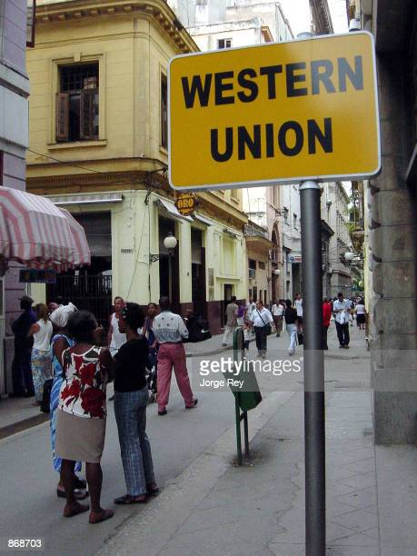 People walk by the Western Union office June 27 2002 in Havana Cuba Supporters of end to the US travel ban to Cuba in the US Congress say they think...
