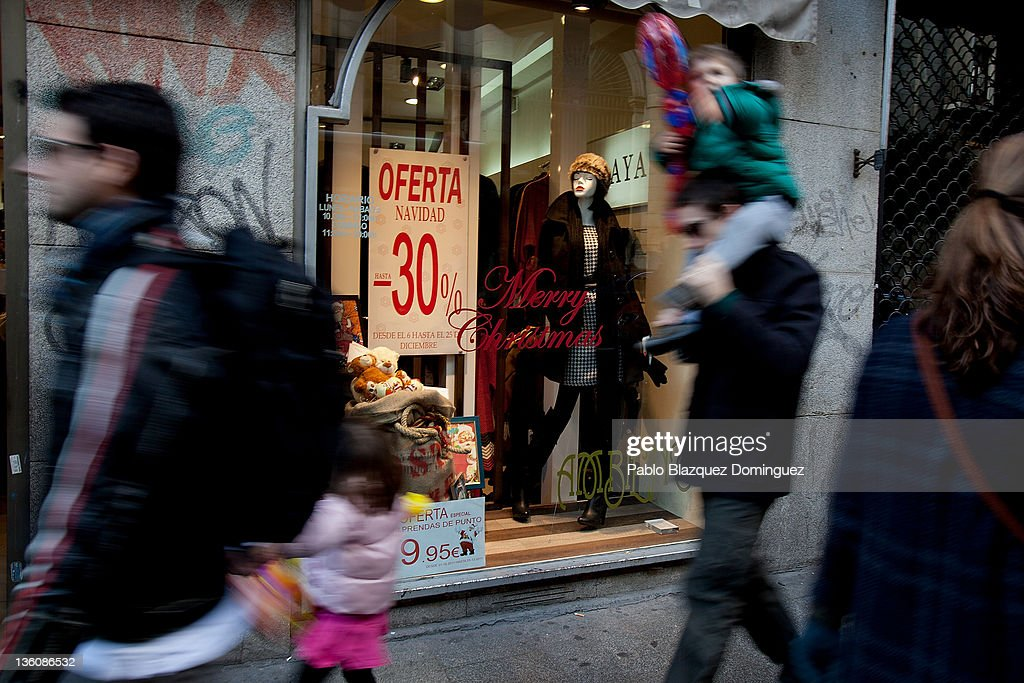 People walk by the window display of a shop offering sales to shoppers six days before Christmas Day on December 19, 2011 in Madrid, Spain. This year businesses are starting sales and discounts before Christmas to try and gain customers during the current economic crisis.