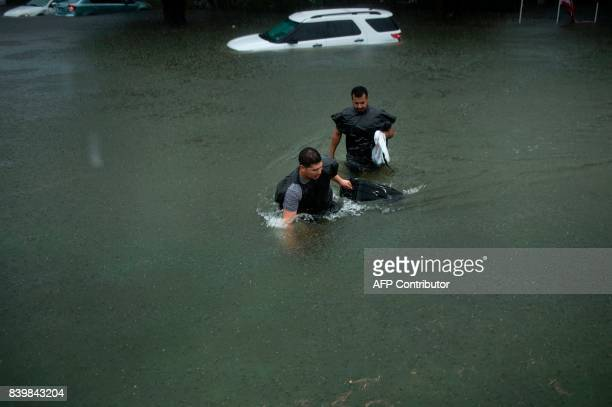 TOPSHOT People walk dogs through flooded streets as the effects of Hurricane Harvey are seen August 27 2017 in Galveston Texas Hurricane Harvey left...
