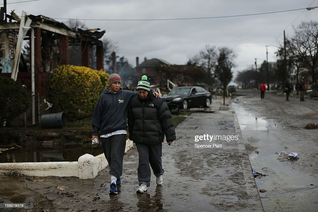 People walk down a block which was heavily damaged after Hurricane Sandy on October 30, 2012 in the Rockaway section of the Queens borough of New York City. At least 40 people were reportedly killed in the U.S. by Sandy as millions of people in the eastern United States have awoken to widespread power outages, flooded homes and downed trees. New York City was hit especially hard with wide spread power outages and significant flooding in parts of the city.