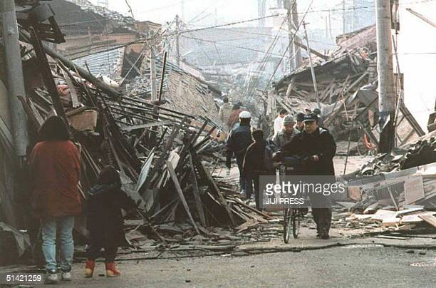 People walk down a devastated Kobe street 18 January following the earthquake that hit western Japan 17 January The National Police Agency said over...