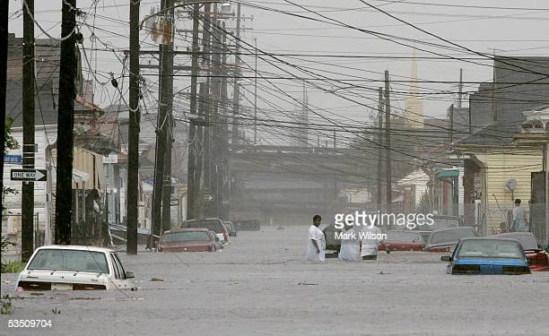 People walk down a flooded street after Hurricane Katrina hit the area August 29 2005 in New Orleans Louisiana Katrina was down graded to a category...