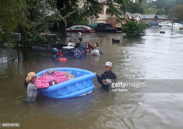 People walk down a flooded street as they evacuate their homes after the area was inundated with flooding from Hurricane Harvey on August 28 2017 in...