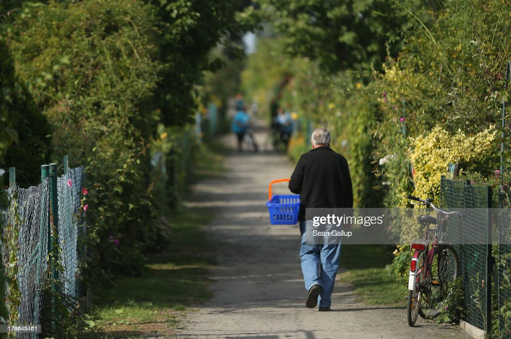 People walk down a path separating gardens at the Oeynhausen Small Garden Association garden colony on August 29, 2013 in Berlin, Germany. At the Oeynhausen colony about 300 of its 438 gardens are currently threatened by real estate development, as are about another 24 colonies across the city. Berlin has about 900 garden colonies that are owned by the city and that provide urban dwellers who don't have land of their own the opportunity to maintain a garden and escape the stress of urban life. Berlin is currently undergoing a housing squeeze and city authorities are beginning to sell some of the colonies to developers, which has caused outrage in a city where the colonies of small gardens are a deep-seated tradition going back over a century.