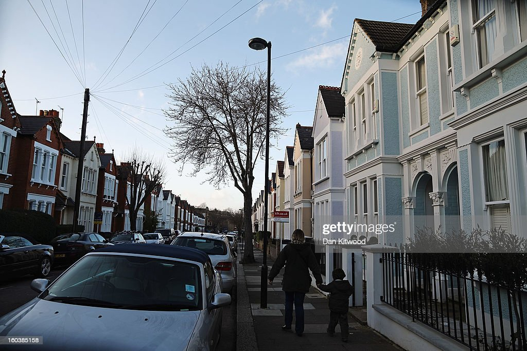 People walk down a residential street in Clapham on January 30, 2013 in London, England. According to a report from independent analysts Oxford Economics, the average mortgage deposit for first-time buyers in London, is likely to exceed £100,000 GBP by 2020.