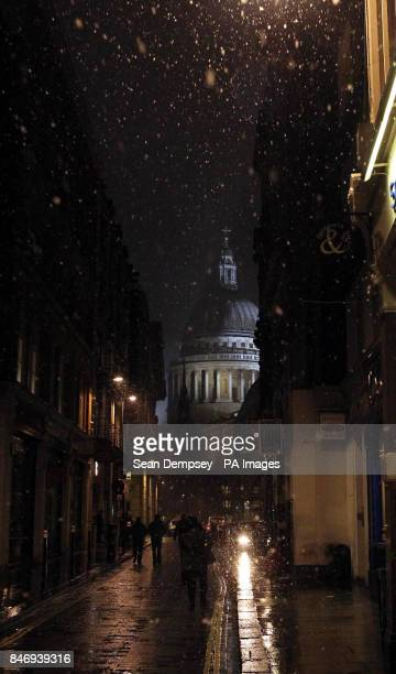 People walk down a road in the snow towards St Paul's Cathedral in London as up to four inches of snow is expected to fall in parts of England and...