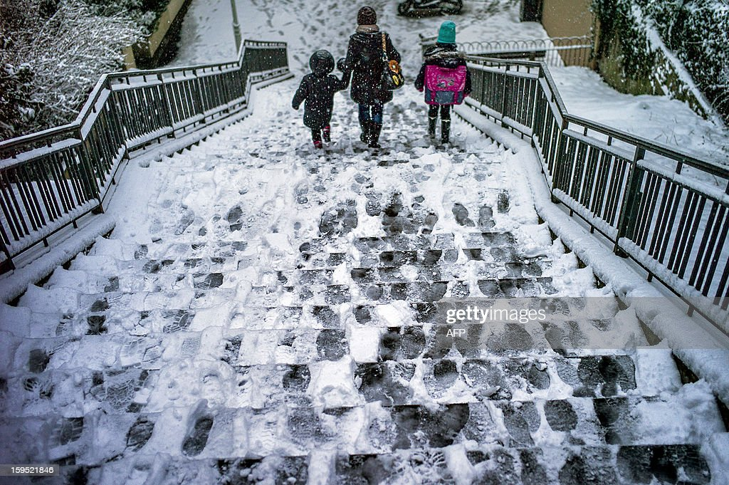 People walk down a snow covered stairway, on January 15, 2013, in a street of Lyon, central eastern France, after snow blanketed several French departments.