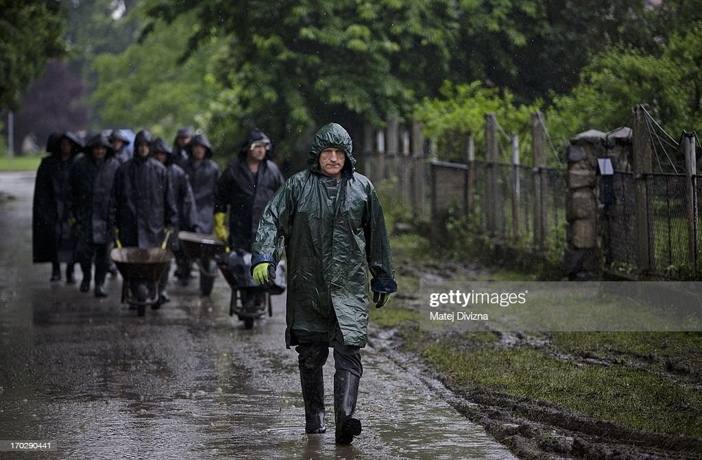 People walk down a street during a rainy day after flooding from Vltava River on June 10, 2013 in Luzec, Czech Republic. As river levels in Czech Republic decrease expectations of flooding increase in Northern Germany triggering more evacuations.