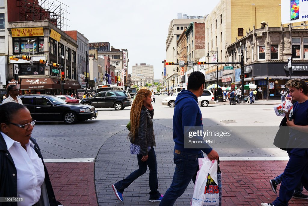 People walk down a street in downtown on May 13 2014 in Newark New Jersey Voters in New Jersey's largest city go to the polls on May 13 to choose a...