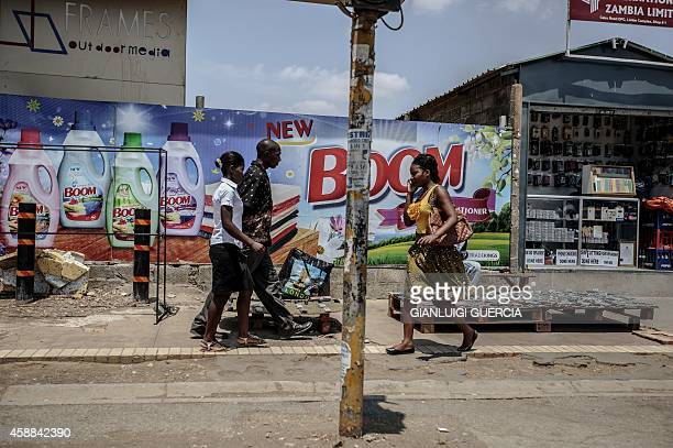 People walk down a street in the central Lusaka Businness district on November 12 a day after the burial of the late Zambian president AFP...