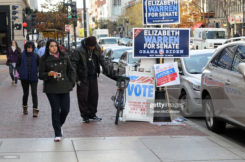 People walk down Boylston Street outside a voting location November 6, 2012 in Boston, Massachusetts. The race between incumbent President Barack Obama and Republican challenger Mitt Romney will come down to certain swing states like New Hampshire. Photo by Darren McCollester/Getty Images)