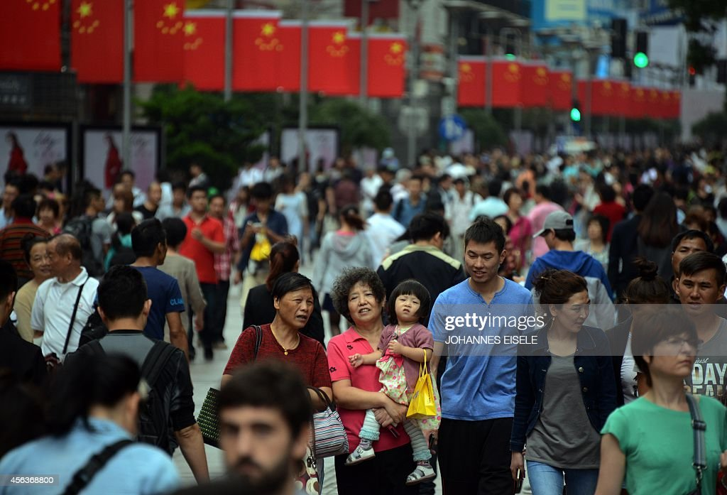 People walk down Nanjing Road during rush hour in Shanghai on September 30 2014 Police will patrol across the city to ensure security during the...