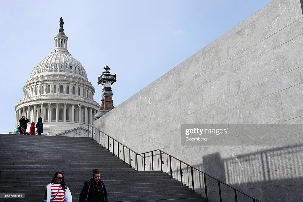 People walk down steps in front of the U.S. Capitol building in Washington, D.C., U.S., on Friday, Dec. 28, 2012. The U.S. House will hold its first Sunday session in more than two years as lawmakers seek to resolve a budget impasse before at least $600 billion in spending cuts and tax increases begin Jan. 1. Photographer: David Rogowski/Bloomberg via Getty Images