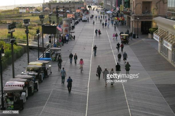 People walk down the boardwalk September 15 2014 in Atlantic City New Jersey The Trump Plaza which opened on May 14 shut down September 16 the fourth...