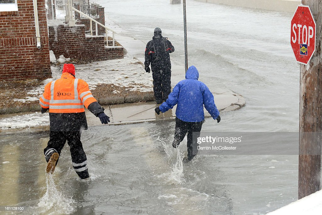 People walk down Winthrop Shore Drive through flood waters February 9, 2013 in Winthrop, Massachusetts. An overnight blizzard dropped two to three feet of snow, with coastal flooding expected as the storm lingers into the day.