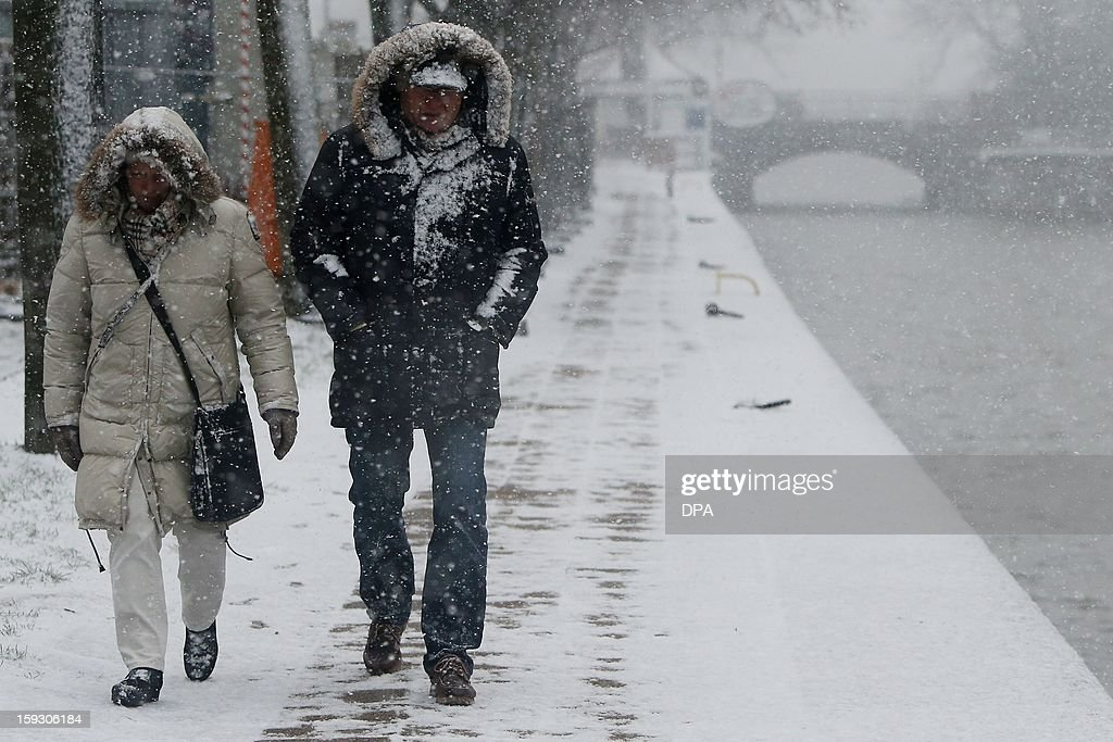 People walk during a snowfall on January 11, 2013 in Luebeck, northern Germnay.