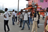People walk during clashes between police forces and students demanding the payment of scholarships funds in Libreville on April 18 2012 AFP PHOTO /...