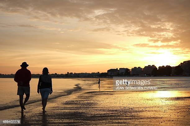 People walk during sunset on the beach of La Baule western France on September 6 2014 AFP PHOTO / JEANSEBASTIEN EVRARD