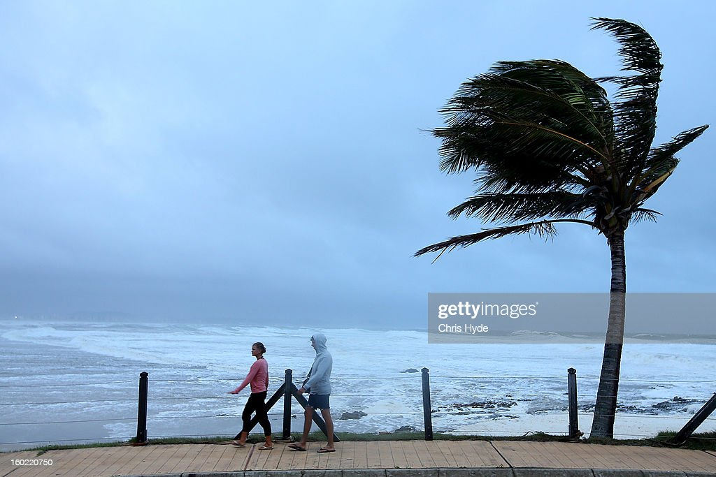 People walk during wild conditions at Snapper Rocks as Queensland experiences severe rains and flooding from Tropical Cyclone Oswald on January 28, 2013 in Gold Coast, Australia. Hundreds have been evacuated from the towns of Gladstone and Bunderberg while the rest of Queensland braces for more flooding.