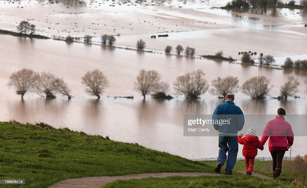 People walk from Glastonbury Tor as flood water in the fields below is seen, on November 25, 2012 in Somerset, England. Another band of heavy rain and wind continued to bring disruption to many parts of the country today particularly in the south west which was already suffering from flooding earlier in the week.