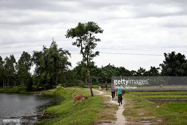 People walk from the Bash Kata Indian enclave into Bangladesh July 9 2015 in Lalmonirhat District Bangladesh The India Bangladesh enclaves also known...