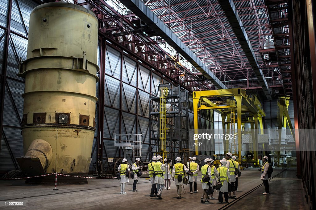 People walk in a corridor of the Eurodif SA/George Besse 1 uranium enrichment plant on May 31 2012 in SaintPaulTroisChateaux southeastern France The...