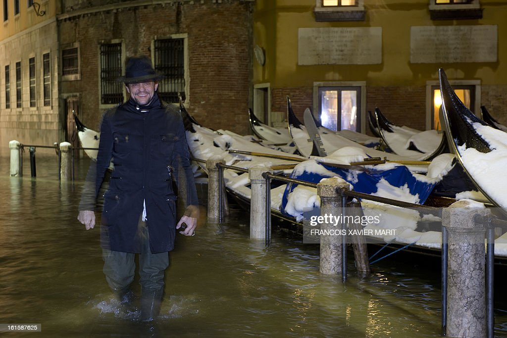 People walk in a flooded street during an acqua-alta (high-water) late on February 11, 2013 in Venice. The 'acqua alta', a convergence of high tides and a strong sirocco, reached 143 centimetres around midnight.