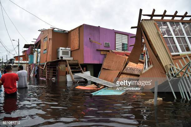 People walk in a flooded street next to damaged houses in Juana Matos Catano Puerto Rico on September 21 after Hurricane Maria slammed into the...