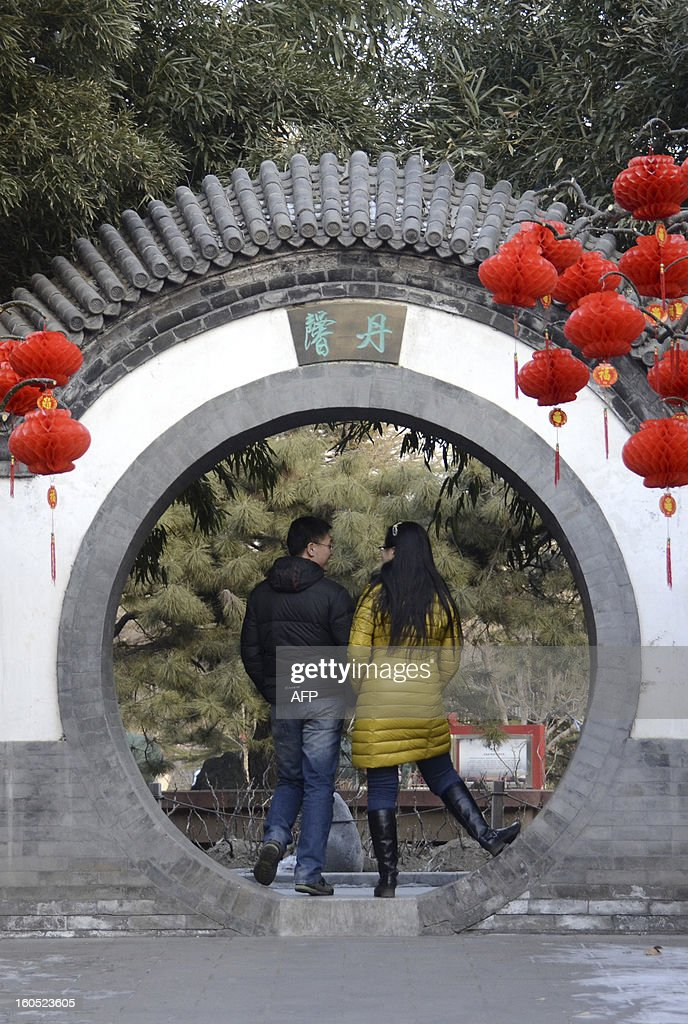 People walk in a park decorated with colorful decals for the upcoming Lunar New Year, at a park in Beijing on February 2 , 2013. The Chinese New Year know locally as the Spring Festival, causes the world's largest annual migration of people with millions of travellers boarding public transport to journey across the vast country for the Lunar New Year celebrations. The government estimates the number of passenger trips on trains, planes, boats and buses will reach 3.2 billion during the holiday, up 9.1 percent from last year. AFP PHOTO / WANG ZHAO
