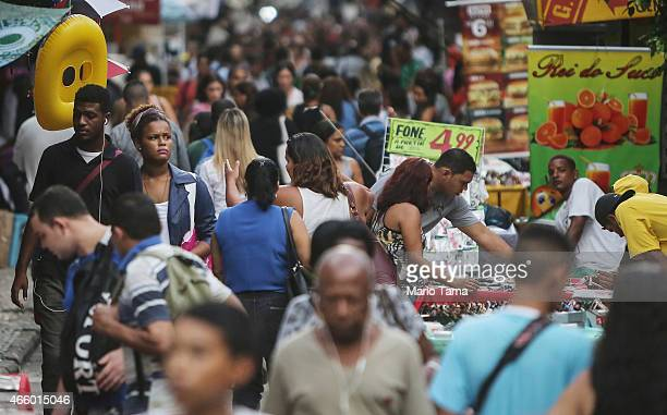 People walk in a shopping disctrict in the Centro neighborhood on March 12 2015 in Rio de Janeiro Brazil Brazil's inflation rate has hovered around...