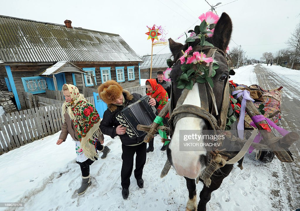 People walk in a street covered with snow as they attend Christmas celebrations in the town of Richev, some 290 km south from Minsk, on January 7, 2013. Orthodox Christians celebrate Christmas on January 7 in the Middle East, Russia and other Orthodox churches that use the old Julian calendar instead of the 17th-century Gregorian calendar adopted by Catholics, Protestants, Greek Orthodox and commonly used attendsin secular life around the world.