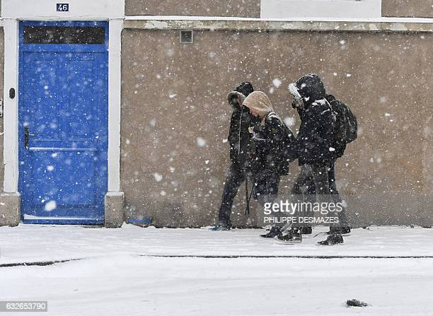 People walk in a street during a snowfall on January 25 2017 in Montelimar southeastern France / AFP / PHILIPPE DESMAZES