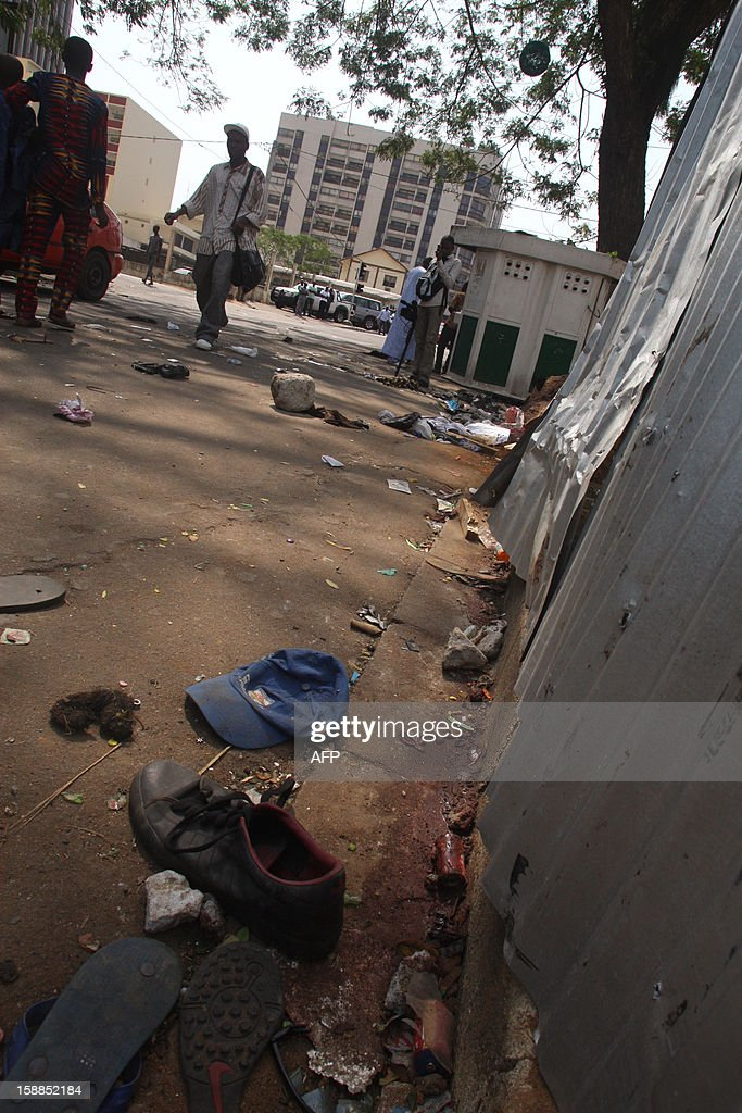 People walk in a street in Abidjan as shoes and various items are seen on the pavement at the scene of a stampede, on January 1, 2013. At least 60 people died and at least dozens were injured as crowds stampeded overnight during celebratory New Year's fireworks, Ivory Coast rescue workers said on January 1, 2013. AFP PHOTO/HERVE SEVI