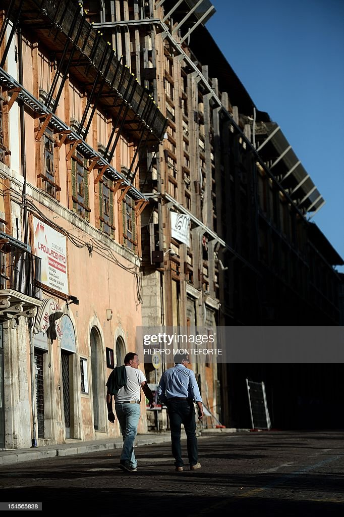 People walk in a street on October 22 2012 in L'Aquila Six Italian scientists and a government official were found guilty the same day of multiple...