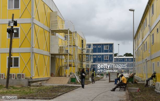 People walk in an alley past the dormitory at the National Institute of Youth and Sports on July 17 2017 in the Marcory neighbourhood in Abidjan...