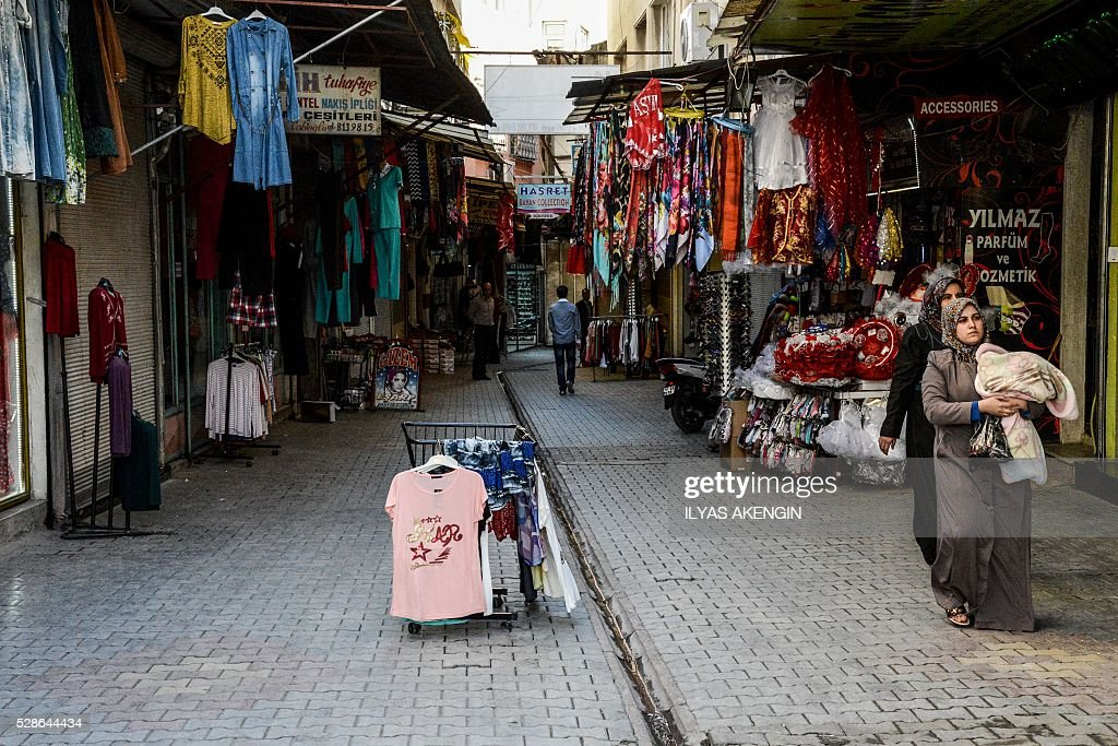 People walk in an almost empty shopping street of Kilis on May 6, 2016 after several rockets targeted it in the past days. One person was killed and seven more wounded on May 5, 2016 when rockets fired from Syria slammed into the Turkish border region of Kilis, which has been regularly targeted by jihadists this year, the Dogan news agency said. / AFP / ILYAS