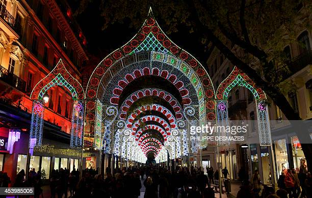 People walk in an illuminated street in Lyon central eastern France on December 6 2013 during the 15th edition of the 'Fête des Lumières' a secular...