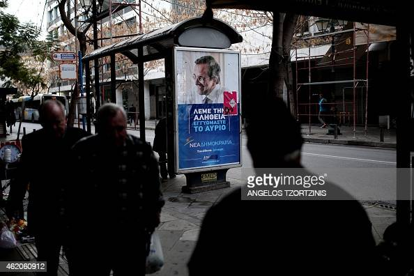 People walk in Athens on January 24 2015 in front of campaign posters of Greek Prime minister Antonis Samaras of the conservative New Democracy party...