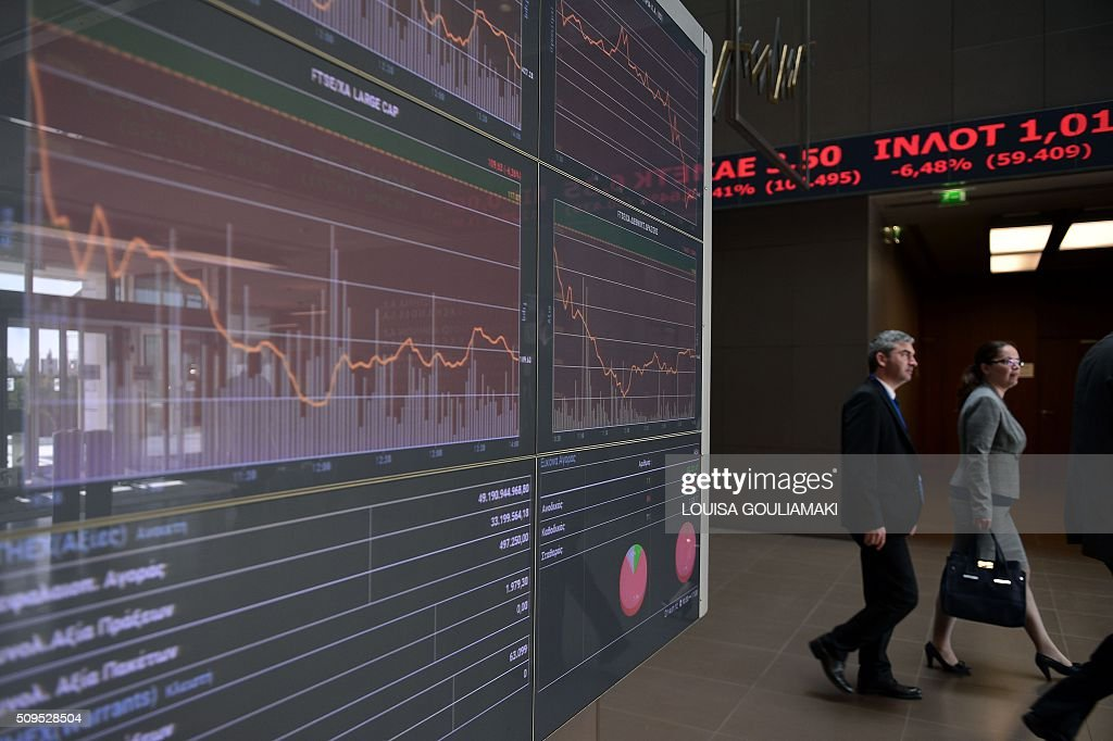People walk in Athens stock exchange on February 11, 2016. Greek stocks shed over 6 percent in value amid a broader European slide fueled by oil price worries and global economy fears. The Athens stock exchange fell to 421.25 points at around midday, with the economic climate in Greece also burdened by concerns over the country's tortuous reform talks with its EU-IMF creditors. / AFP / LOUISA GOULIAMAKI