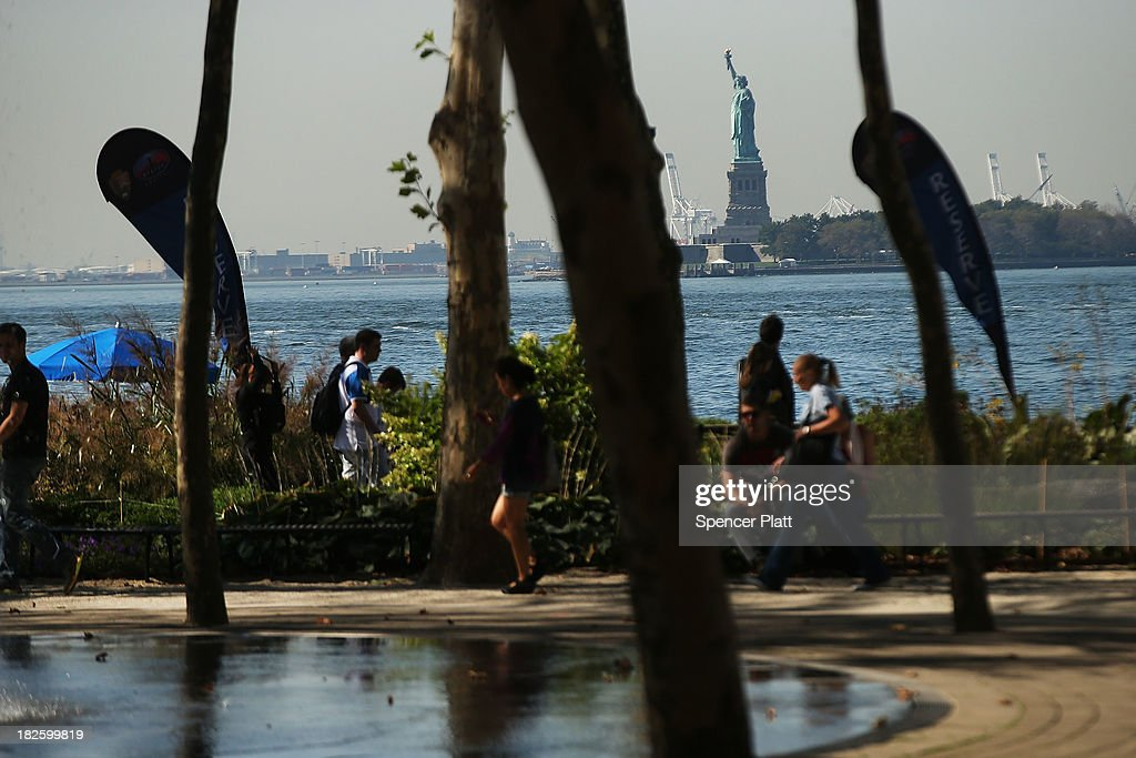People walk in Battery Park as the Statue of Liberty remain closed in the background due to the government shutdown on October 1, 2013 in New York City. Federal museums and parks across the nation are closed starting today due to a government shutdown for the first time in nearly two decades. The Dow Jones industrial average, the S&P 500 and the Nasdaq all rose slightly higher in early trading Tuesday morning.