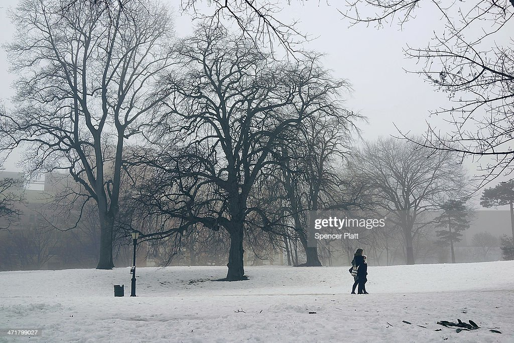 People walk in Brooklyn's Fort Greene Park in the fog on February 21, 2014 in New York City. After weeks of bitter cold weather and heavy snow, New York and much of the Northeast got a break from winter with warming temperatures. The forecast calls for temperatures to remain warm through the weekend before falling back down next week.