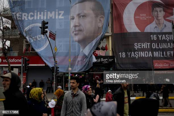 People walk in front of a building displaying a large banner of Turkish President Recep Tayyip Erdogan outside a 'Yes' referendum campaign rally...