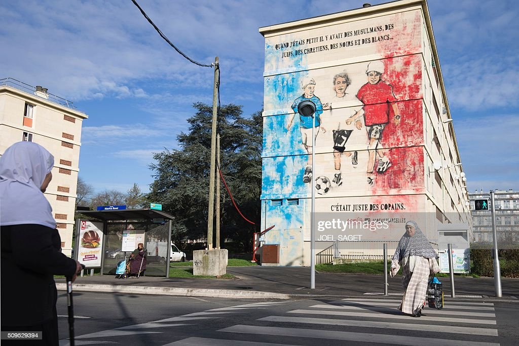 People walk in front of a building with a fresco created by French street artist combo displaying the words 'When I was a kid, there were Muslims, Jewish, Christians, Blacks and Whites... They were just friends' on February 11, 2016 in Sarcelles, northern suburb of Paris. / AFP / JOEL SAGET / RESTRICTED TO EDITORIAL USE - MANDATORY MENTION OF THE ARTIST UPON PUBLICATION - TO ILLUSTRATE THE EVENT AS SPECIFIED IN THE CAPTION