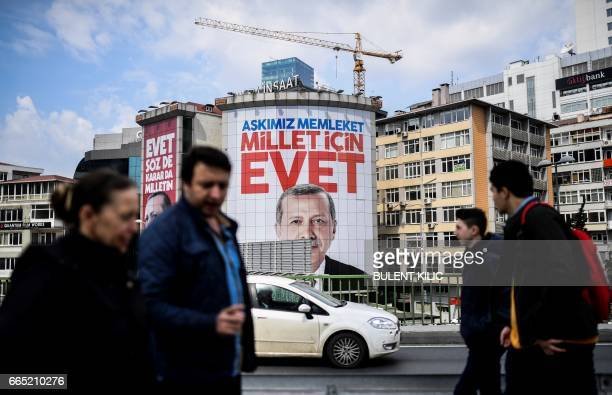 People walk in front of a giant poster of Turkish President on April 6 2017 in Istanbul 10 days ahead of the referendum on whether to change the...