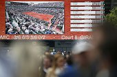 People walk in front of a giant screen at the Roland Garros 2015 French Tennis Open in Paris on May 25 2015 AFP PHOTO / PATRICK KOVARIK