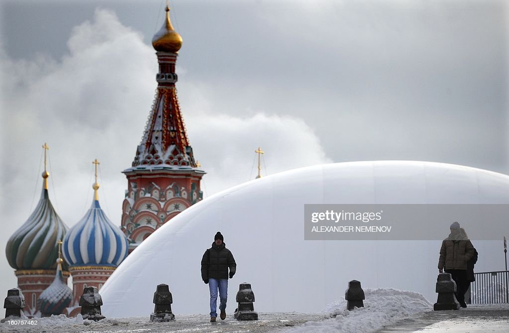 People walk in front of a huge temporary dome covering the mausoleum of Soviet state founder Vladimir Lenin on Red Square, in Moscow, on February 5, 2013. The dome keeps temperatures inside warmer and allows repair works on the mausoleum to continue even during winter to finish them by the end-of-April deadline. AFP PHOTO / ALEXANDER NEMENOV