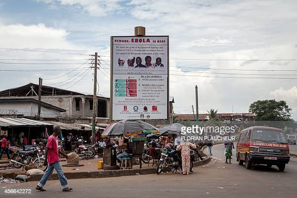 People walk in front of a poster warning against the deadly Ebola virus in a street of Freetown on October 4 2014 The Ebola epidemic has infected...