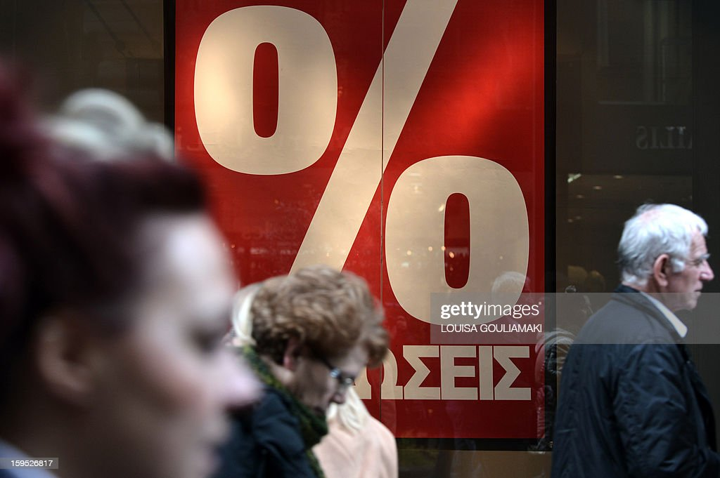 People walk in front of a 'sales' sign at a shop in central Athens, on the first day of winter sales in Greece on January 15, 2013. The eurozone will shortly clear the next slice of bailout funding for Greece worth 9.2 billion euros, with Athens satisfying conditions for the payment, EU sources said on Tuesday. AFP PHOTO/ Louisa Gouliamaki